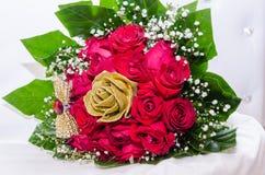 Un ramo de rosas frescas rojas y de rosas artificiales de oro con la cinta, gotas y hojas del verde en una silla blanca Fotografía de archivo libre de regalías