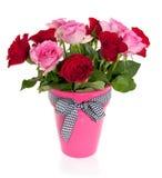 Un ramo de rosas rojas y rosadas en un florero rosado Foto de archivo