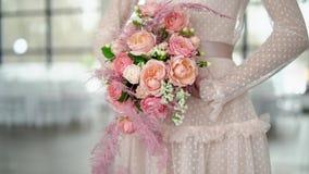 Un ramo de rosas y de joyería coral-coloreada en las manos del bride-2 metrajes
