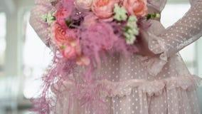 Un ramo de rosas y de joyería coral-coloreada en las manos de la novia almacen de video