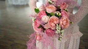 Un ramo de rosas y de joyería coral-coloreada en las manos de la novia metrajes