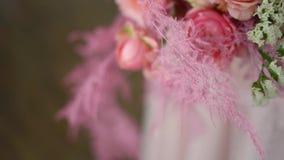 Un ramo de rosas y de joyer?a coral-coloreada en las manos de la novia metrajes