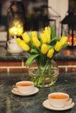 Un ramo de tulipanes amarillos en un florero dentro de un retro Fotos de archivo libres de regalías
