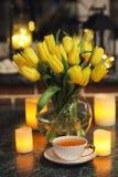 Un ramo de tulipanes amarillos en un florero dentro de un retro Fotos de archivo