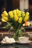 Un ramo de tulipanes amarillos en un florero dentro de un retro Imagenes de archivo