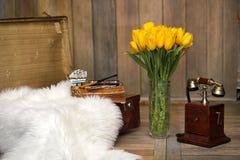 Un ramo de tulipanes amarillos en un florero dentro de un retro Fotografía de archivo libre de regalías