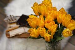 Un ramo de tulipanes amarillos en un florero dentro de un retro Imagen de archivo