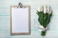 Un ramo de tulipanes blancos con la tableta en los tableros de madera azules foto de archivo