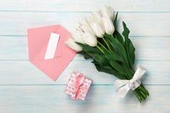 Un ramo de tulipanes blancos con una caja de regalo, una nota del amor y un sobre del color en los tableros de madera azules imagenes de archivo