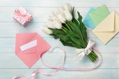 Un ramo de tulipanes blancos y una cinta rosada bajo la forma de corazón con una caja de regalo, una nota del amor y un sobre del fotografía de archivo libre de regalías