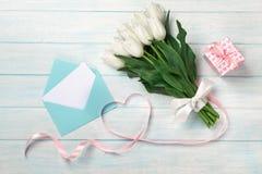 Un ramo de tulipanes blancos y una cinta rosada bajo la forma de corazón con una caja de regalo, una nota del amor y un sobre del foto de archivo