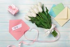 Un ramo de tulipanes blancos y una cinta rosada bajo la forma de corazón con una caja de regalo, una nota del amor y un sobre del foto de archivo libre de regalías