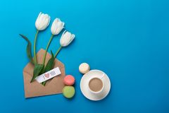 Un ramo de tulipanes blancos y de una taza de café con una nota del amor y de macarons en un fondo azul fotos de archivo libres de regalías