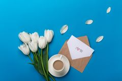 Un ramo de tulipanes blancos y de una taza de café con una nota del amor sobre un fondo azul imagen de archivo libre de regalías