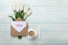 Un ramo de tulipanes blancos y de una taza de café con una nota del amor sobre los tableros de madera azules imagen de archivo