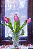 Un ramo de tulipanes en un florero por la ventana foto de archivo libre de regalías