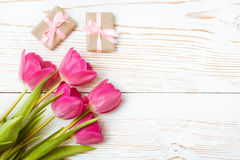 Un ramo de tulipanes frescos y de un par de regalos embalados con una cinta rosada en un fondo de madera blanco Imagen de archivo