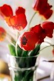 Un ramo de tulipanes rojos en un florero en el alf?izar Un regalo al d?a de una mujer de las flores rojas del tulip?n imagen de archivo