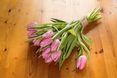 Un ramo de tulipanes rosados en un fondo de madera hermoso rebobinado con una guita del hilo del arte Fotos de archivo libres de regalías