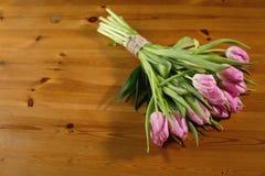Un ramo de tulipanes rosados en un fondo de madera hermoso rebobinado con una guita del hilo del arte Fotografía de archivo