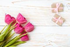 Un ramo de tulipanes rosados frescos y de un par de regalos embalados en un fondo de madera blanco Fotos de archivo libres de regalías