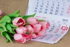 Un ramo de tulipanes rosados que mienten en el calendario Foto de archivo libre de regalías