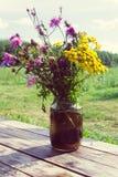 Un ramo de wildflowers en una tabla de madera en un pueblo del verano fotografía de archivo