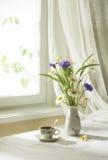 Un ramo de wildflowers y de taza de café Foto de archivo