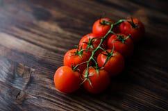 Un ramo dei pomodori ciliegia organici rossi su un fondo di legno Fotografie Stock Libere da Diritti
