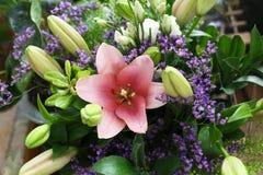 Un ramo hermoso de lirios con un brote rosado grande en el centro fotografía de archivo libre de regalías