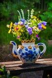 Un ramo hermoso de wildflowers en una tetera grande usada como v Imagen de archivo