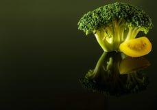 Un ramoscello dei broccoli con una fetta di pomodoro ciliegia giallo immagini stock libere da diritti