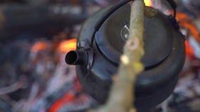 Un randonneur avec le bois de chauffage et une hache approche le feu sur lequel la bouilloire bout clips vidéos