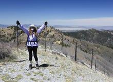 Un randonneur célèbre atteindre le sommet d'une montagne images stock