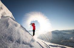 Un randonneur dans les alpes autrichiennes jette une bouteille complètement d'eau bouillante dans le ciel La congélation rapide s photographie stock libre de droits