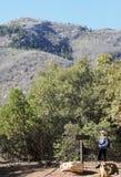 Un randonneur de femme lit un signe de Trailhead Images libres de droits