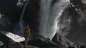 Un randonneur masculin marche à une cascade dans le mouvement lent banque de vidéos