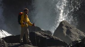 Un randonneur masculin observe une grande cascade dans le mouvement lent banque de vidéos