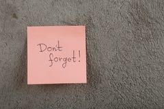 un rappel - don' ; t oublient ?crit sur des notes d'autocollant de couleur sur le fond de ciment images libres de droits