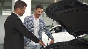 Un rappresentante professionista informa un compratore di un motore di automobile immagini stock libere da diritti