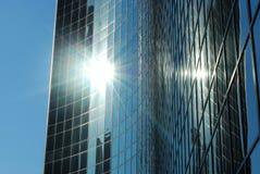Un rascacielos de cristal con el sol que relucir Foto de archivo libre de regalías