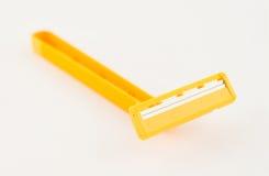 Un rasoio giallo su bianco Fotografia Stock