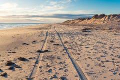 Un rastro de dos ruedas de un coche condujo a lo largo de la playa ancha imagenes de archivo