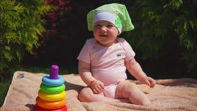 Un recién nacido feliz se está sentando en una toalla en el parque, es después una pirámide del juguete almacen de metraje de vídeo