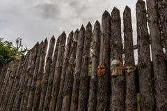 Un recinto fatto dei pali di legno con le visiere dei caschi medievali inchiodati a  fotografie stock libere da diritti