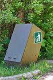 Un recipiente para residuos de la prueba del oso al lado de algunos árboles Foto de archivo libre de regalías