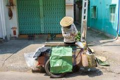 Un recolector que recoge las cajas del cartón en una pequeña calle, Saigon, Vietnam Imagen de archivo