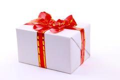 Un rectángulo de regalo blanco con la cinta roja Imágenes de archivo libres de regalías