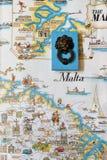 Un recuerdo maltés masivo típico contra el contexto de un mapa turístico del vintage de Malta foto de archivo