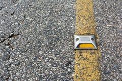 Un reflector en la carretera de asfalto Imagen de archivo